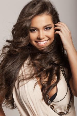cabello rizado: Retrato de una mujer sonriente con el pelo largo castaño saludable y maquillaje fresco peinado ondulado pelo no aislado en el fondo
