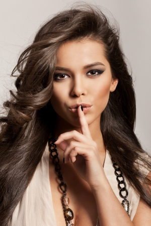 strong wind: Portrait of a beautiful woman with healthy long brown hair and fresh makeup making a hush gesture. Wavy Hair. Hairstyle. Not isolated on grey background. Indoor