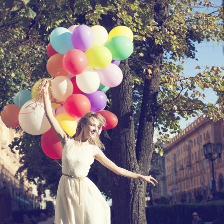 donna innamorata: Felice giovane donna con palloncini colorati in lattice, esterno Archivio Fotografico