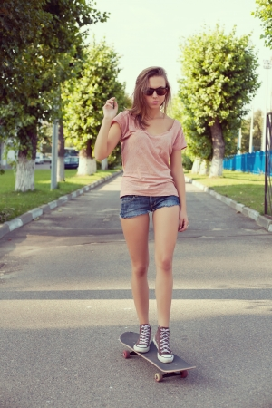 board shorts: Portrait of a woman with a skateboard on street, outdoors