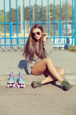 Young woman with blue roller skates, outdoors photo