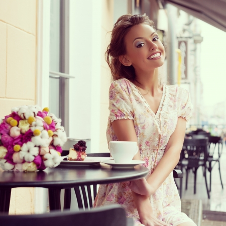 cafe table: Happy beautiful young woman drinking coffee  Outdoors