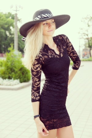 sexy black dress: Portrait of pretty woman wearing black dress and straw hat in sunny warm weather day  Walking at summer park  Outdoors