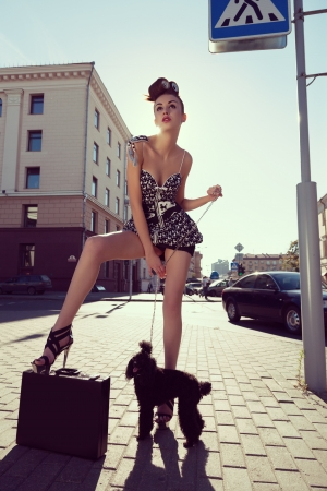 Sensual woman and dog standing on street  Outdoors photo