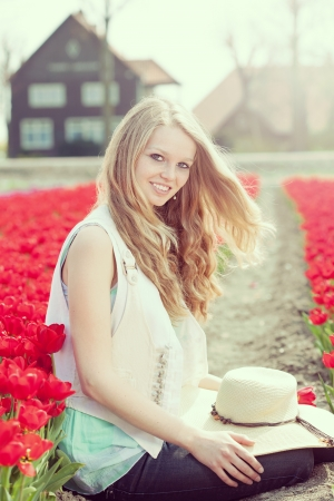 beautiful woman with hat in her hands on the meadow with red flowers tulips, outdoors photo