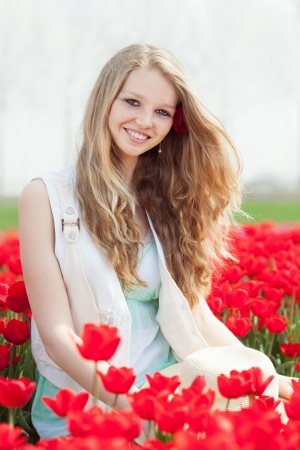 dutch girl: happy young woman with hat on the meadow with red flowers tulips, outdoors