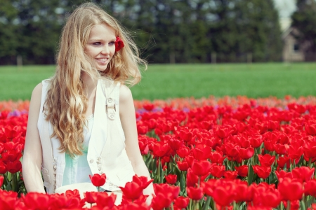 Beautiful young woman on the field with red flowers tulips, outdoors Stock Photo