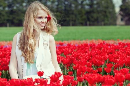 Schöne junge Frau auf dem Feld mit roten Blumen Tulpen, im Freien