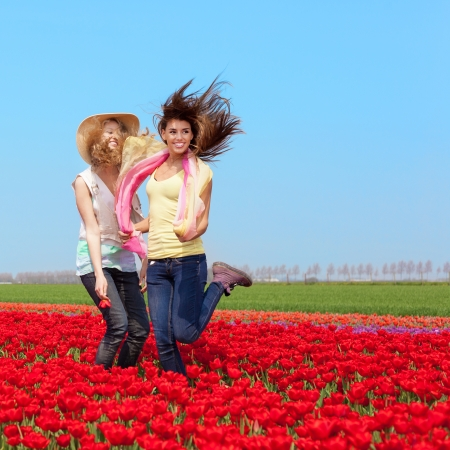 two beautiful young girls jumping in a red tulip field, outdoors photo