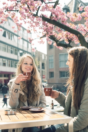 Two pretty girl-friends talk and drink coffee in cafe, outdoors photo