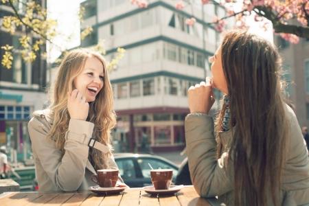giggle: Dos mujeres j�venes hablan y beben caf� en caf�, al aire libre Foto de archivo