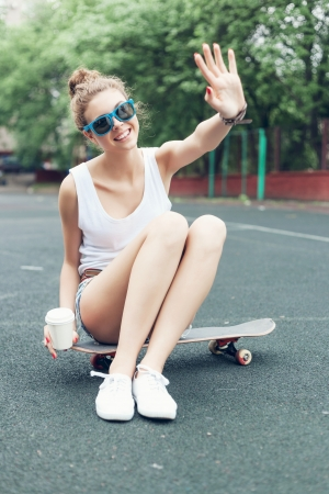 girl in shorts: Pretty woman sitting on skateboard and waving by hand in the daytime, outdoors