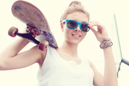 girl in shorts: Young woman in blue sunglasses standing with a skateboard in her hands in the daytime
