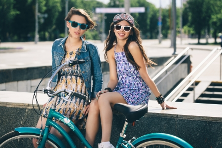 spring fashion: Two beautiful young women in sunglasses relaxing on a warm summer day Stock Photo
