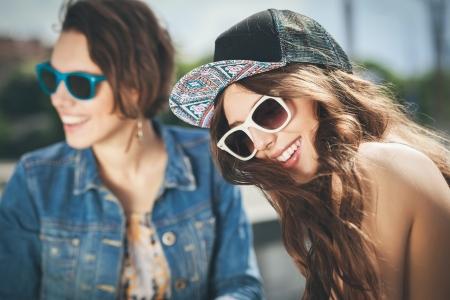 mode: Zwei schöne glückliche Mädchen in Sonnenbrille auf dem städtischen Hintergrund