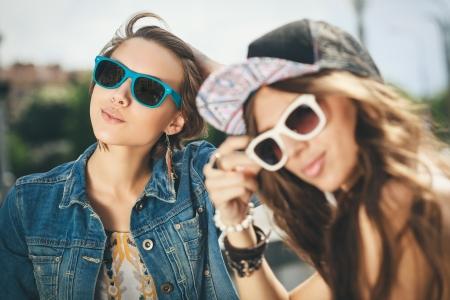 sexy teenage girls: Two happy girls in sunglasses looking into the distance on the urban background Stock Photo