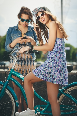 sexual activities: Two beautiful young women in sunglasses relaxing on a warm summer day Stock Photo