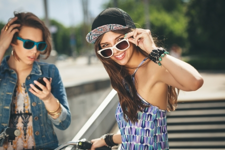 urban youth: Two beautiful girls in sunglasses on the urban background Stock Photo