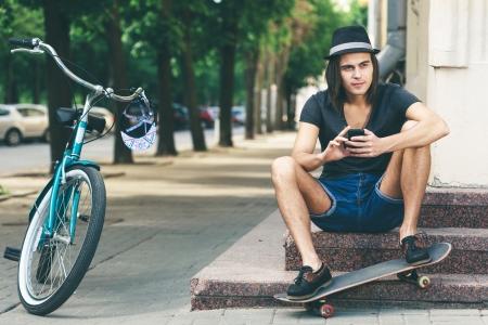 niño en patines: Skater feliz que se sienta en las escaleras