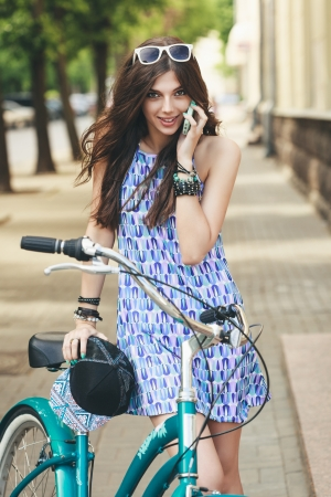Young woman with bike is talking by phone in city photo