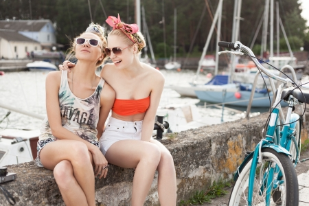 Holiday at the seaside. Two beautiful young women smiling on a pier near yachts. Outdoor, lifestyle photo