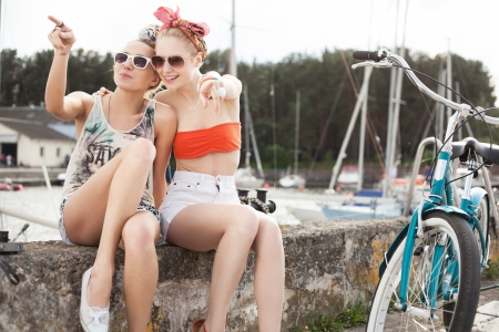 Holiday at the seaside. Two beautiful women on a pier near yachts. Outdoor, lifestyle photo