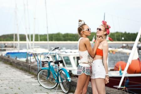 pin up vintage: Vacanza al mare. Due donne divertenti baciare su un molo vicino yacht. Outdoor, stile di vita Archivio Fotografico