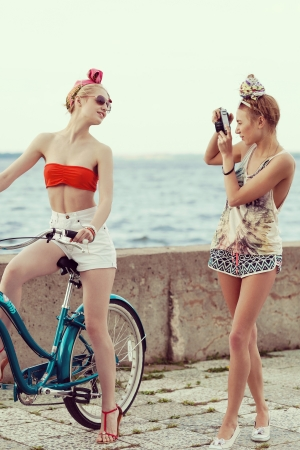 girl on bike: Young woman taking a picture with an old camera against a pier. Outdoor, lifestyle