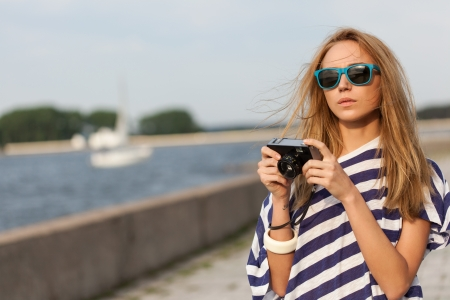 Pretty girl taking a picture with an old camera against a pier near sea. Outdoor, lifestyle photo