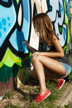 Beautiful girl is drawing a graffiti on a wall. Outdoors, lifestyle