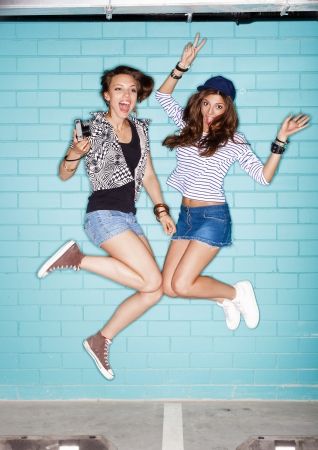 two young women jumping against blue wall. Lifestyle