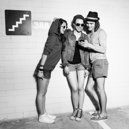 Three young friends looking at the pictures on the phone. Lifestyle Stock Photo - 21000468