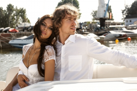 Fashion lovely beautiful couple posing on the luxury boat in open sea in summer. Young man and sensual brunette outdoor portrait in classic dress near the ocean. Outdoors, lifestyle. photo
