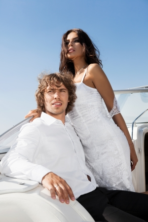 Fashion lovely couple posing on the luxury boat in open sea in summer. Young man and sensual brunette outdoor portrait in classic dress near the ocean. Outdoors, lifestyle. photo