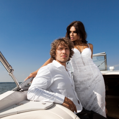 lovely beautiful couple posing on the luxury boat in open sea in summer. Young man and sensual brunette outdoor portrait in classic dress near the ocean. Outdoors, lifestyle. photo