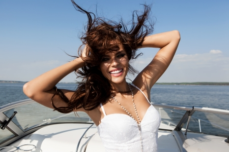 yacht people: Boat young woman smiling happy looking at the sea sailing by. Caucasian female model. Outdoors, lifestyle. Stock Photo