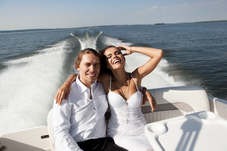 Fashion lovely beautiful couple smiling on the luxury boat in open sea in summer. Young man and sensual brunette outdoor portrait in classic dress near the ocean. Outdoors, lifestyle. photo