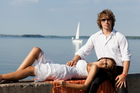Fashion lovely beautiful couple sitting in the hot sun on the pier near the boats and yachts in summer. Young man and sensual brunette outdoor portrait in classic dress near the ocean. Outdoors, lifestyle. photo