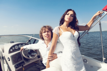 Fashion lovely beautiful couple posing on the luxury boat in open sea in summer. Young man and sensual brunette outdoor portrait in classic dress. Outdoors, lifestyle. photo