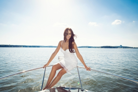 Young happy beautiful woman looking at the camera on the luxury boat in open sea in summer. Caucasian female model. Outdoors, lifestyle.