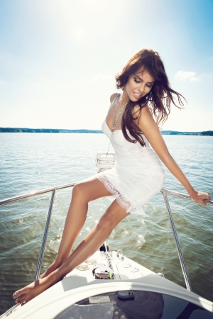 Young pretty woman enjoying on the luxury boat in open sea in summer. Caucasian female model. Outdoors, lifestyle. photo