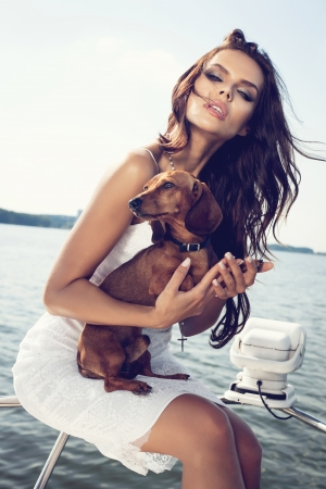 happy woman with dog on the luxury boat in open sea in summer. Caucasian female model. Outdoors, lifestyle.