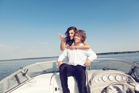 Sexy lovely couple on the luxury boat in open sea in summer. Young man and sensual brunette outdoor portrait in classic dress. Outdoors, lifestyle. photo