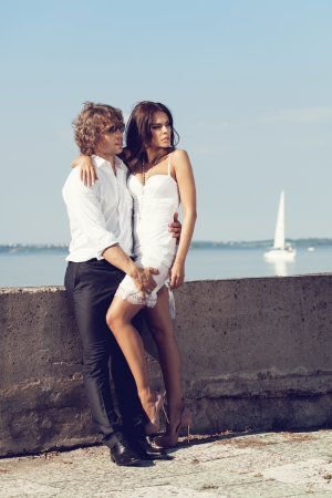 Fashion lovely beautiful couple standing in the hot sun on the pier in summer. Young man and sensual brunette outdoor portrait in classic dress near the ocean. Outdoors, lifestyle. photo