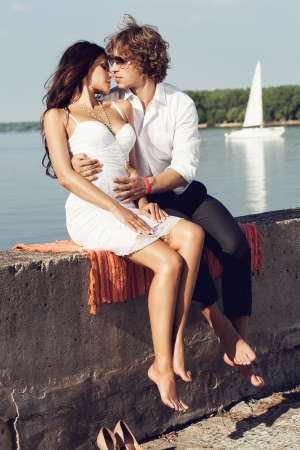 lovely couple kissing in the hot sun on the pier in summer. Young man and sensual brunette outdoor portrait in classic dress near the ocean. Outdoors, lifestyle. Stock Photo