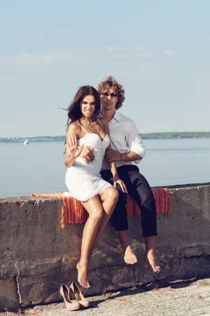 lovely beautiful couple sitting in the hot sun on the pier in summer. Young man and sensual brunette outdoor portrait in classic dress near the ocean. Outdoors, lifestyle. photo