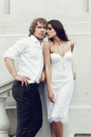 Fashion lovely couple posing in the old part of town. Young man and sensual brunette outdoor portrait in classic dress. Outdoors, lifestyle. photo