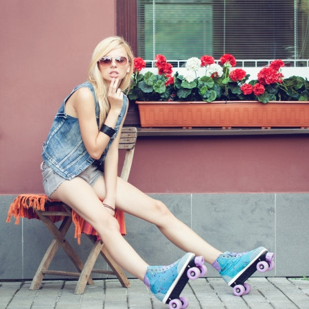 Young blonde woman in roller skates sitting on the chair. Beautiful smiling girl summer portrait  toned with tender summer yellow color. Outdoors. lifestyle Stock Photo - 22384879
