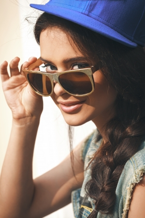 Closeup of Young sexy girl in blue cap and jeans jacket  looking through golden sunglasses .  Outdoors, lifestyle. Stock Photo