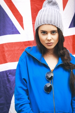 british girl: Beautiful young brunette girl in stylish clothes and sunglasses with national british flag in background. Outdoors, Lifestyle Stock Photo